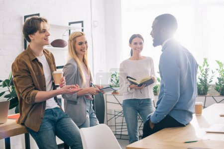 Photo pour Entrepreneurs multiculturels avec café et manuels scolaires se réunissant dans un bureau moderne - image libre de droit