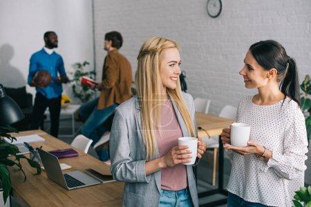 Photo pour Femmes d'affaires souriants avec les tasses à café et hommes d'affaires debout derrière avec ballon - image libre de droit