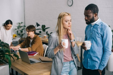 multicultural business coworkers with coffee cups having discussion and two coworkers working on laptop behind