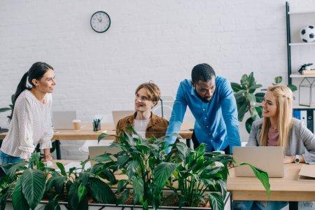 Foto de Empresarios multiétnicos en mesa con ordenadores portátiles en la oficina moderna - Imagen libre de derechos