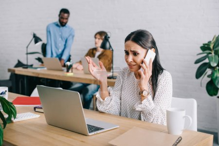 Photo for Upset businesswoman talking on smartphone and colleagues working behind in modern office - Royalty Free Image