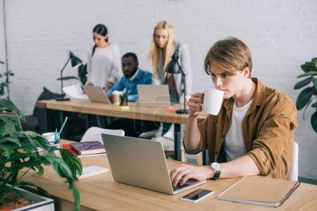 Photo pour Homme d'affaires avec tasse de café à l'aide d'un ordinateur portable et collègues travaillant derrière dans un bureau moderne - image libre de droit