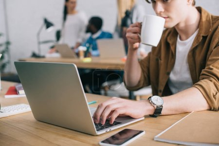 Photo for Cropped shot of young businessman drinking coffee and using laptop at table and colleagues working behind - Royalty Free Image