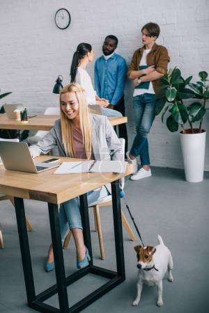 smiling businesswoman using laptop and holding jack russell terrier on leash and coworkers having meeting behind in modern office