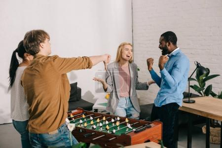 multiethnic businesspeople playing table football and doing different gestures in modern office