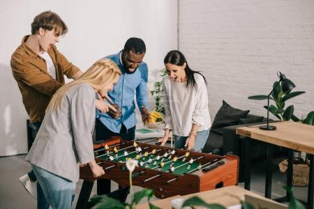 businesswomen playing table football and two male colleagues pointing on board game