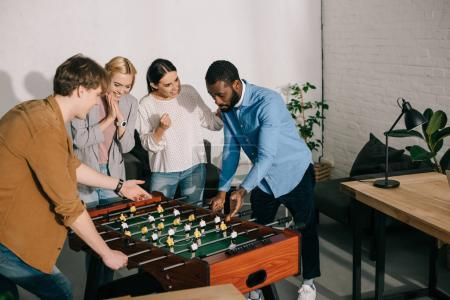 multiethnic businessmen playing table football and female colleagues cheering up them