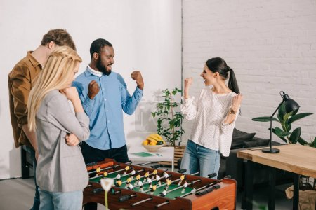 two business colleagues celebrating victory in table football in front of losing coworkers
