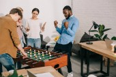 african american celebrating victory in table football and colleagues standing near