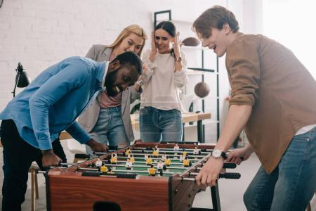 side view of happy multicultural businessmen playing table football in front of female colleagues