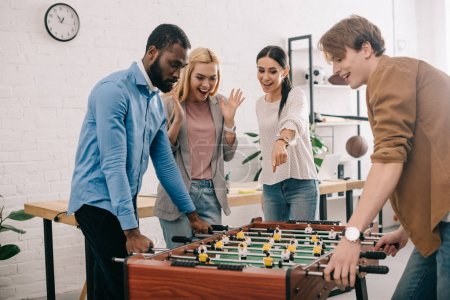 side view of multicultural businessmen playing table football and female coworker pointing on board game