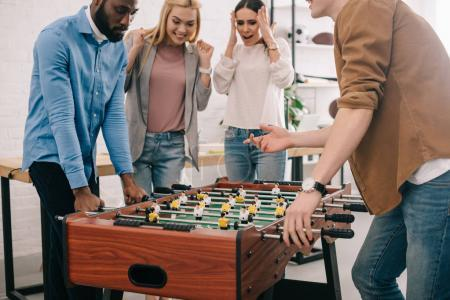 cropped image of businessmen playing table football in front of female colleagues