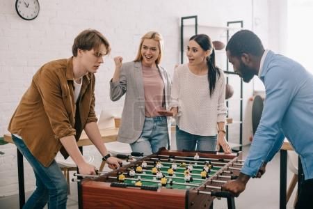 side view of multicultural businessmen playing table football in front of female colleagues