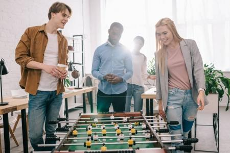 smiling multiethnic businesspeople going to play table football in modern office