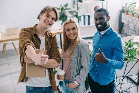 Photo pour Vue sur un angle élevé des entrepreneurs multiethniques heureux avec les pouces vers le haut et le café dans le bureau moderne - image libre de droit