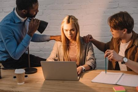 two multicultural businessmen threatening and shine lamp in face of businesswoman using laptop