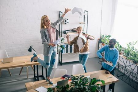 high angle view of happy multiethnic business colleagues throwing papers and having fun in modern office