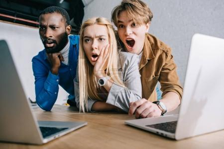 shocked multicultural business colleagues watching on laptop screen