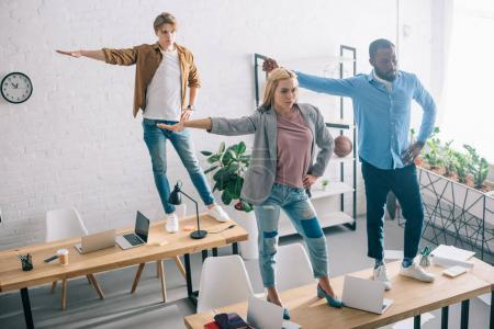 Photo for High angle view of happy multiethnic business colleagues having fun and dancing on tables in modern office - Royalty Free Image