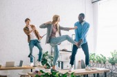 businessman taking picture of multiethnic business colleagues fighting on table in modern office