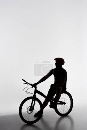 silhouette of trial biker relaxing on bicycle on white