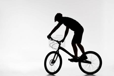 silhouette of trial biker in helmet balancing on bicycle on white