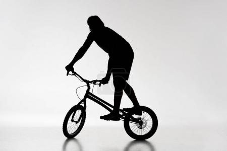 silhouette of trial biker balancing on bicycle on white