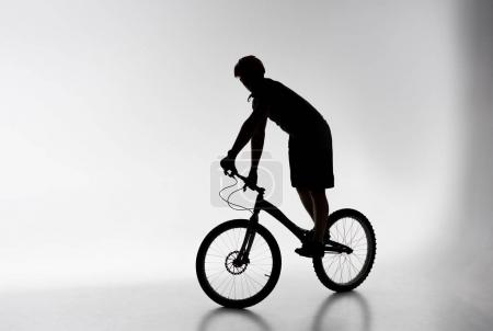 silhouette of trial cyclist in helmet balancing on bicycle on white