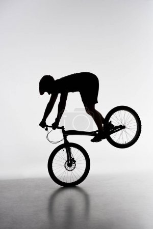 silhouette of trial biker performing front wheel stand on white