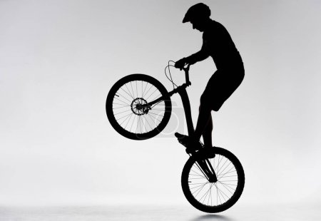 silhouette of trial biker performing bunny hop on white