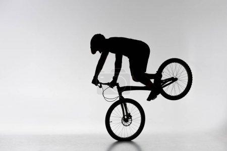 Silhouette von Trial-Radler führt Vorderradständer auf weiß
