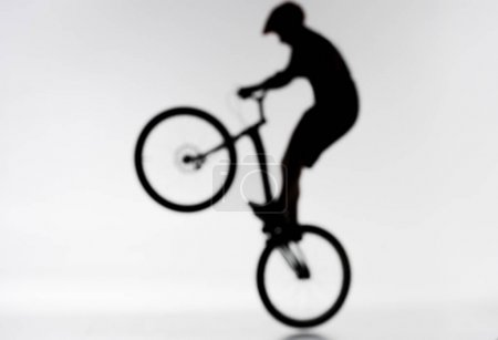 blurred shot of silhouette of trial biker performing bunny hop on white