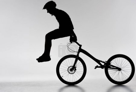 silhouette of trial biker performing stunt on bicycle on white
