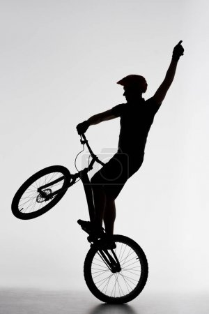 silhouette of trial cyclist standing on back wheel and raising hand on white