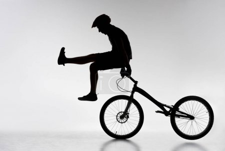 silhouette of trial cyclist standing on handlebars with hands on white