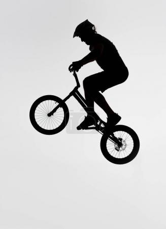 silhouette of trial biker jumping on bicycle on white