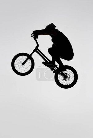 silhouette de cycliste trial sautant sur vélo sur blanc