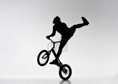 Photo for Silhouette of trial biker performing stunt on bicycle on white - Royalty Free Image