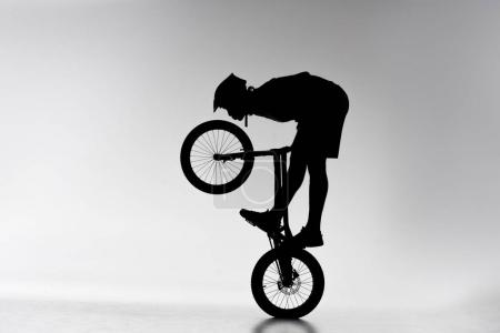 silhouette of trial biker performing balancing stunt on bicycle on white