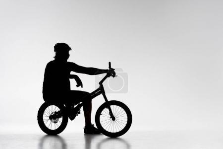 Silhouette von Trial-Biker entspannt auf Fahrrad auf weiß