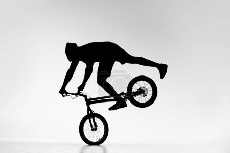 silhouette of trial biker performing front wheel balancing stunt on bicycle on white
