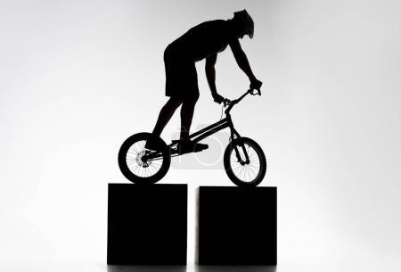 silhouette of trial biker balancing on two stands on white