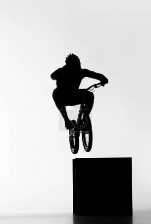 silhouette of trial biker jumping on cube on white