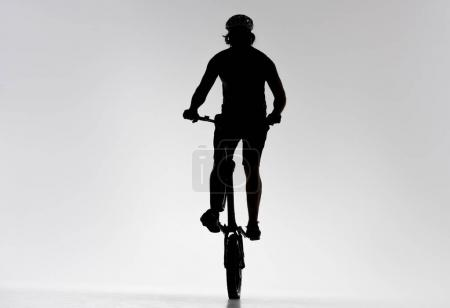 silhouette of trial biker riding on back wheel on white