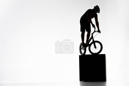 silhouette of trial cyclist balancing on obstacles on white