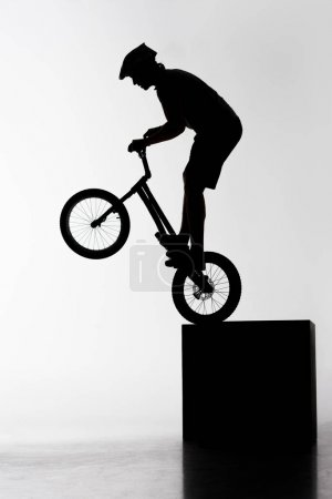 silhouette of trial biker performing stunt while balancing on cube on white