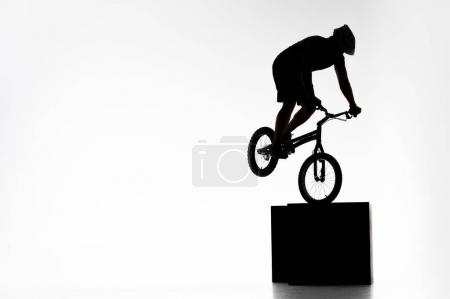 Photo for Silhouette of trial cyclist performing stunt while balancing on cube on white - Royalty Free Image
