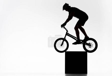 Photo pour Silhouette d'un cycliste du procès d'équilibrage sur cube blanc - image libre de droit
