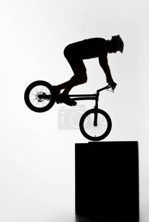 silhouette of trial cyclist performing nollie while balancing on cube on white