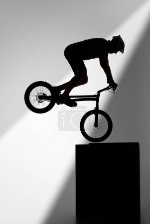Photo for Silhouette of trial cyclist performing stunt while balancing on cube on grey - Royalty Free Image